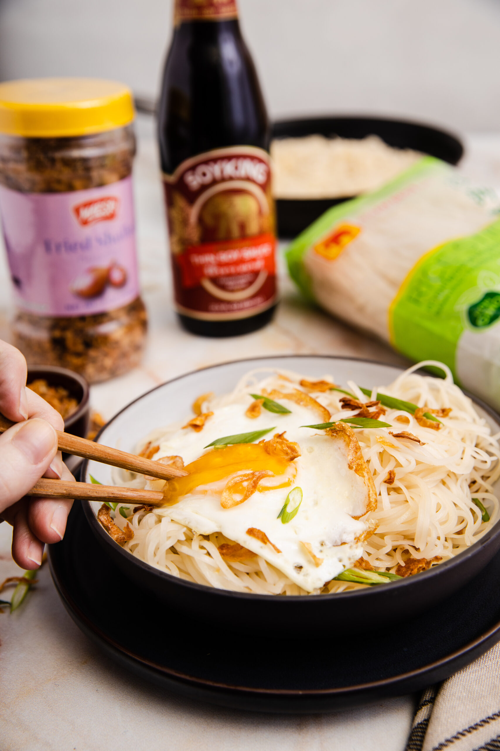 bowl of buttery soy sauce noodles surrounded by packaged noodles, chopsticks, and soy sauce