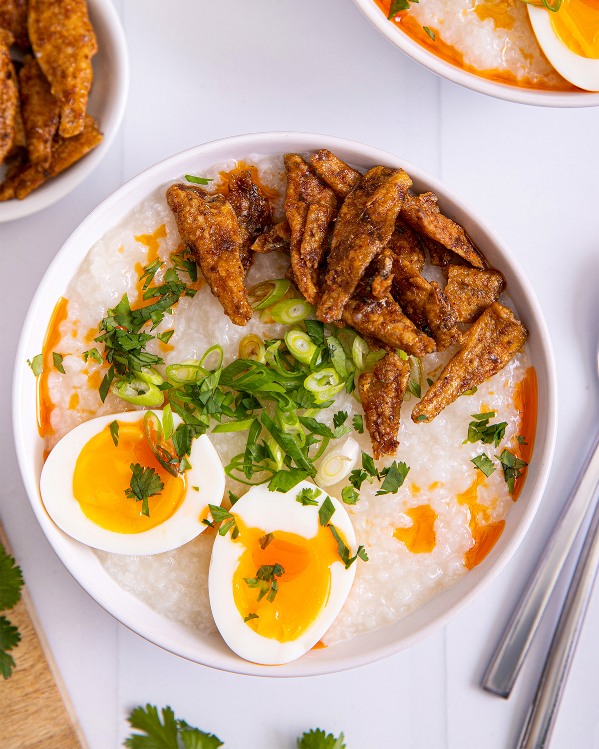 bowl of congee surrounded by chopsticks, bowl of cilantro, uncooked rice
