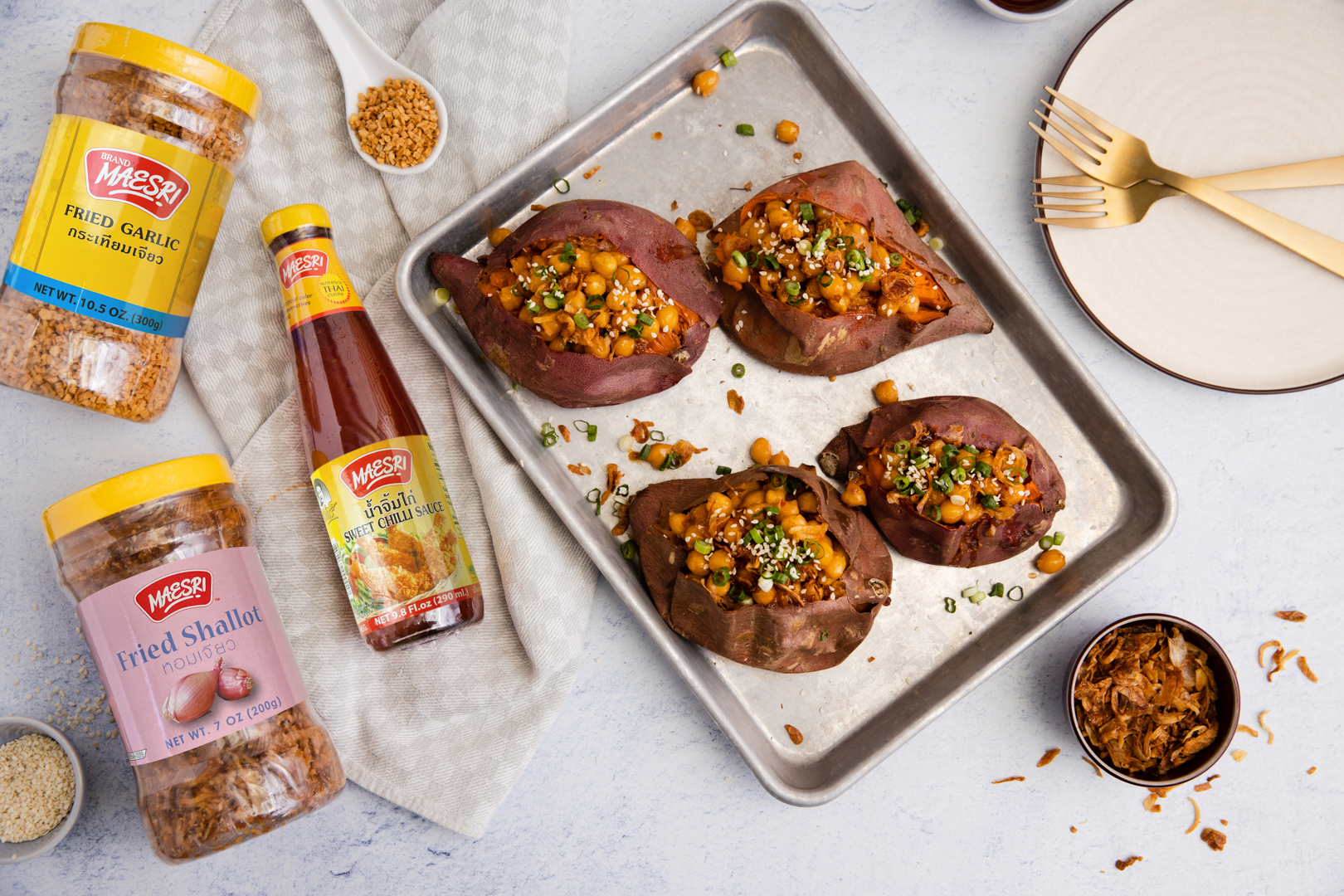 baking tray with fourSticky Chilli Sauce Chickpea-Stuffed Sweet Potatoes