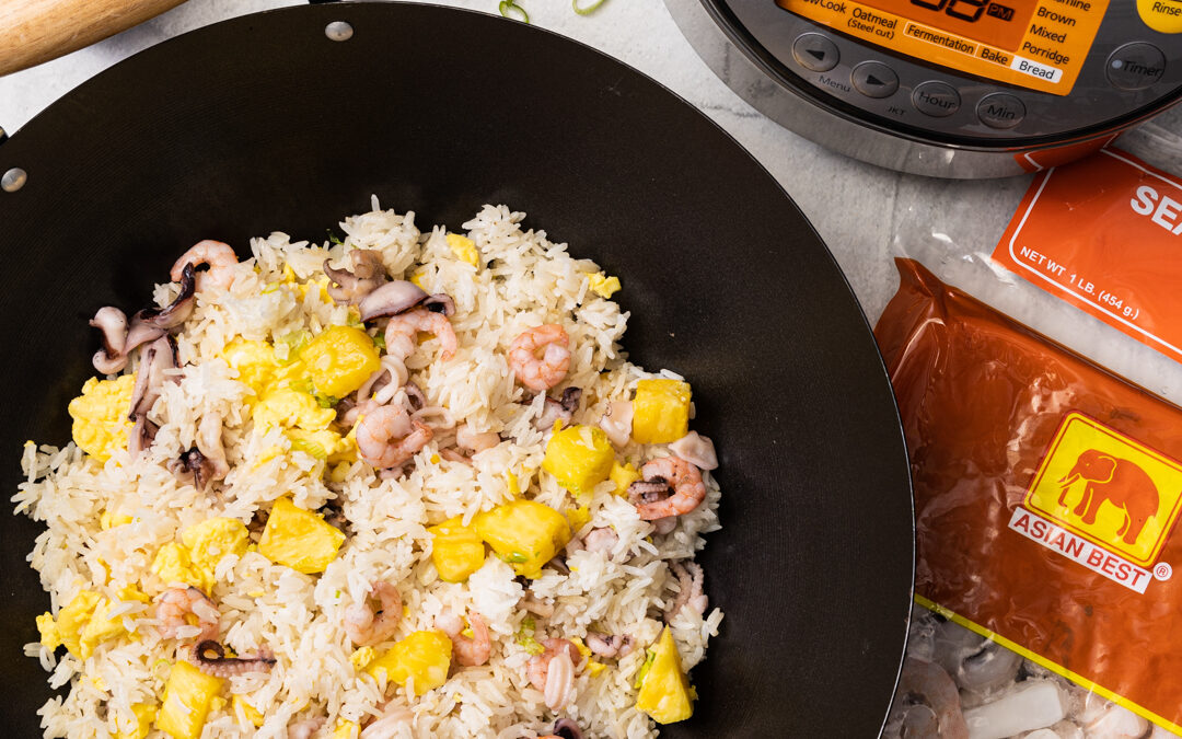 Seafood and Pineapple fried rice in a wok surrounded by a rice cooker, soy sauce bottle, and shrimp